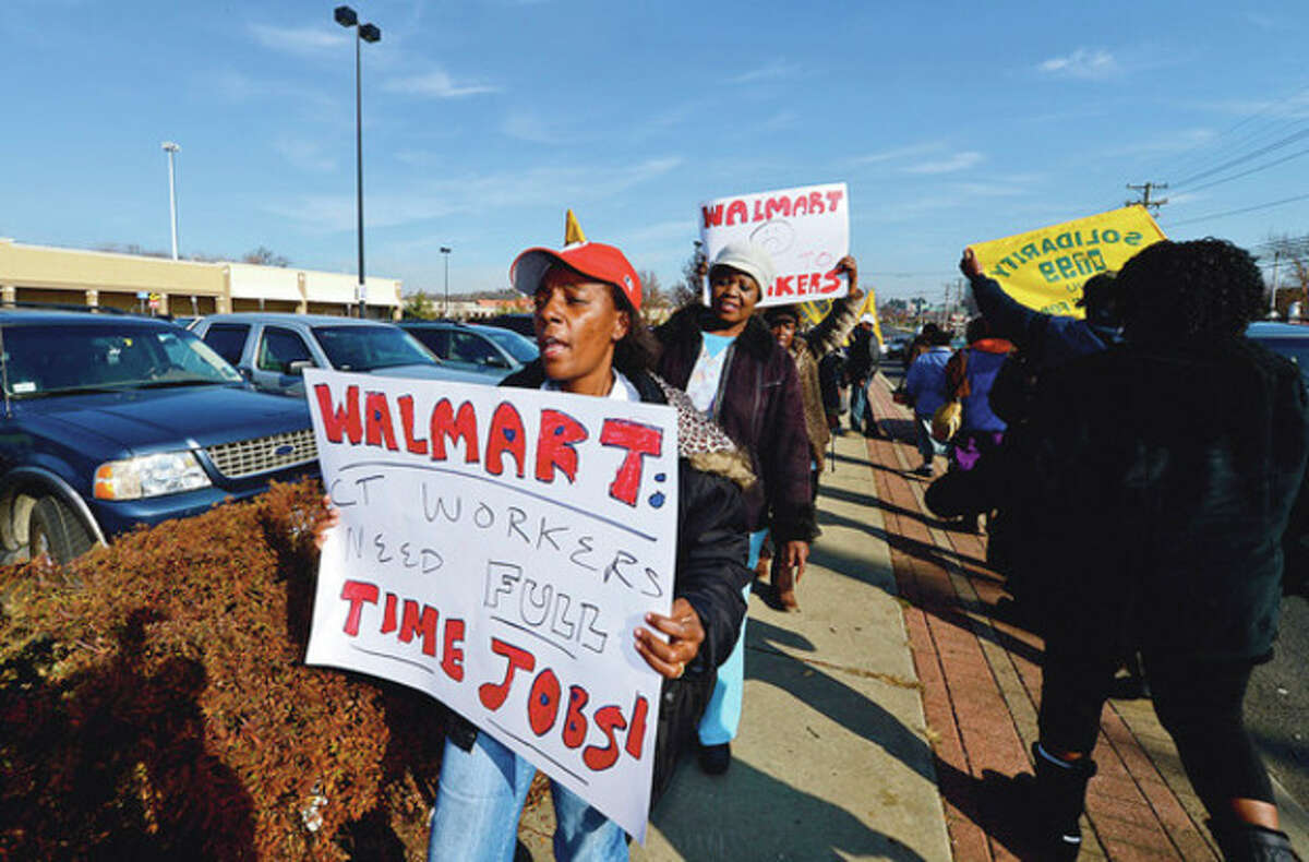 Hour photo / Erik Trautmann Members of local 1199 SEIU Healthcare workers union picket outside Walmart Friday in a protest of poor healthcare for workers there.