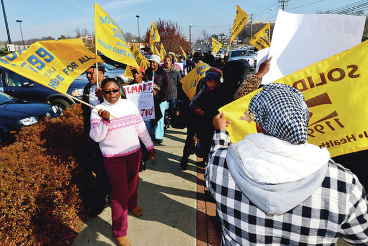 Hour photo / Erik Trautmann Members of local 1199 SEIU Healthcare workers union picket outside Wal-Mart Friday in a protest of poor healthcare for workers there.