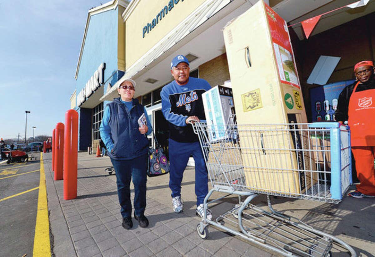 Shoppers including Norwalk resident Edmundo and Edith Arias flock to area stores like Walmart on Black Friday to take advantage of sale pricing. Hour photo / Erik Trautmann