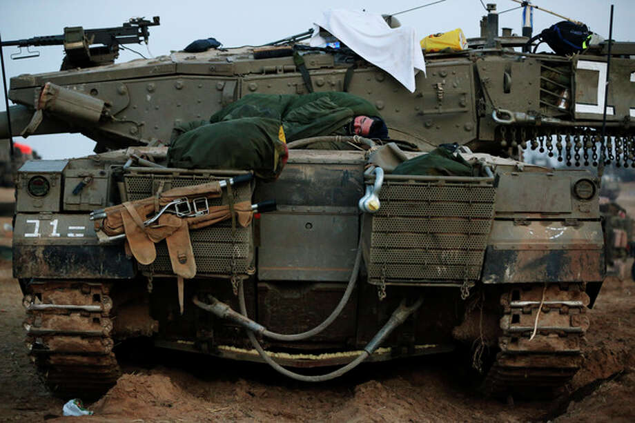 An Israeli soldier sleeps on a tank at a staging area near the Israel Gaza Strip Border, southern Israel, early Tuesday, Nov. 20, 2012. On Tuesday, grieving Gazans were burying militants and civilians killed in ongoing Israeli airstrikes, and barrages of rockets from Gaza sent terrified Israelis scurrying to take cover. Efforts to end a week-old convulsion of Israeli-Palestinian violence drew in the world's top diplomats Tuesday, with U.S. President Barack Obama dispatching his secretary of state to the region on an emergency mission and the U.N. chief appealing from Cairo for an immediate cease-fire. (AP Photo/Lefteris Pitarakis) / AP