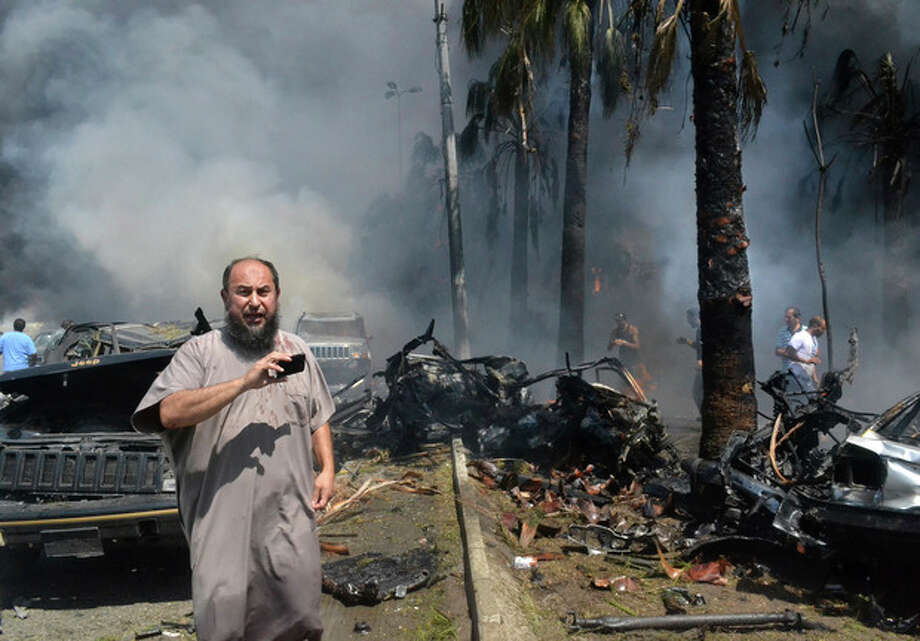 A Lebanese man takes pictures with his mobile phone at the site of an explosion outside a mosque in the Northern city of Tripoli, Lebanon, Friday Aug. 23, 2013. Lebanon's official news agency says dozens of people have been killed by twin explosions outside two Sunni mosques in a northern city. The explosions in Tripoli come amid rising tensions in Lebanon resulting from Syria's civil war, which has sharply polarized the country along sectarian lines and between supporters and opponents of the regime of President Bashar Assad. Tripoli has previously seen clashes between Sunnis and Alawites, a Shiite offshoot sect to which Assad belongs.(AP Photo) / AP