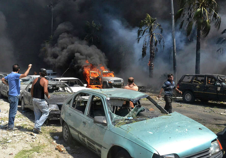 Lebanese men gather at the site of an explosion outside of a mosque, in the northern city of Tripoli, Lebanon, Friday Aug. 23, 2013. Lebanon's official news agency says dozens of people have been killed by twin explosions outside two Sunni mosques in a northern city. The explosions in Tripoli come amid rising tensions in Lebanon resulting from Syria's civil war, which has sharply polarized the country along sectarian lines and between supporters and opponents of the regime of President Bashar Assad. Tripoli has previously seen clashes between Sunnis and Alawites, a Shiite offshoot sect to which Assad belongs. (AP Photo) / AP
