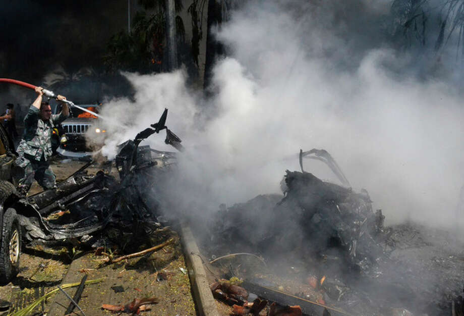 A Lebanese fire fighter, left, extinguishes a burning car at the site of an explosion outside of a mosque, in the northern city of Tripoli, Lebanon, Friday Aug. 23, 2013. Lebanon's official news agency says dozens of people have been killed by twin explosions outside two Sunni mosques in a northern city. The explosions in Tripoli come amid rising tensions in Lebanon resulting from Syria's civil war, which has sharply polarized the country along sectarian lines and between supporters and opponents of the regime of President Bashar Assad. Tripoli has previously seen clashes between Sunnis and Alawites, a Shiite offshoot sect to which Assad belongs.(AP Photo) / AP