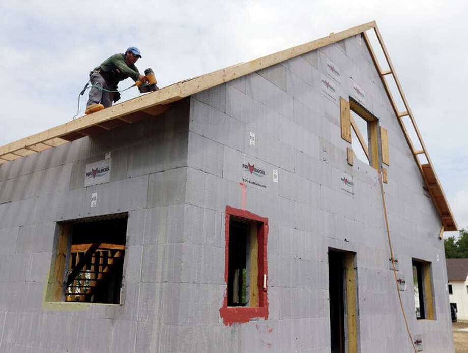 FILE - In this July 9, 2013, file photo, a construction worker drills on the roof of a new home in New Paltz, N.Y. The Commerce Department reports on new-home sales for July, on Friday, Aug. 23, 2013. (AP Photo/Mike Groll, File) / AP