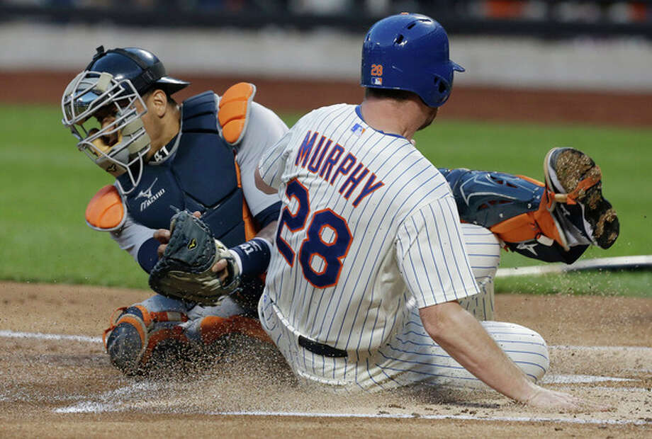 New York Mets' Daniel Murphy (28) slides against Detroit Tigers catcher Victor Martinez to score on a single by Marlon Byrd during the first inning of an interleauge baseball game Friday, Aug. 23, 2013, in New York. (AP Photo/Frank Franklin II) / AP