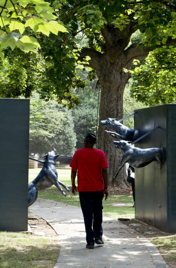 ADVANCE FOR USE SUNDAY, AUG. 25, 2013 AND THEREAFTER - A man walks through a Civil Rights movement sculpture of snarling dogs in Kelly Ingram Park in Birmingham, Ala. on Tuesday, Aug. 6, 2013. (AP Photo/Butch Dill)
