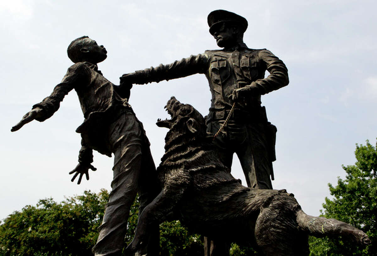 """ADVANCE FOR USE SUNDAY, AUG. 25, 2013 AND THEREAFTER - A young protester confronted by a police officer and a snarling police dog is depicted in a sculpture in Kelly Ingram Park in Birmingham, Ala. on Tuesday, Aug. 6, 2013. As the nation marks the 50th anniversary of the Rev. Martin Luther King Jr.'s """"I Have A Dream"""" speech, there may be no better place than Birmingham to measure the progress that followed the civil rights leader's historic call for racial and economic equality. (AP Photo/Butch Dill)"""