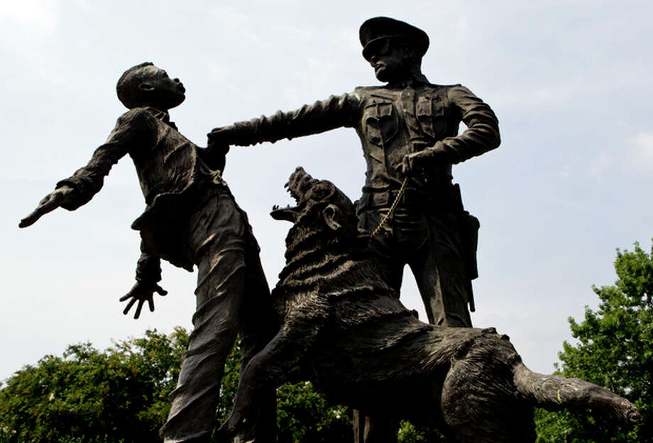 """ADVANCE FOR USE SUNDAY, AUG. 25, 2013 AND THEREAFTER - A young protester confronted by a police officer and a snarling police dog is depicted in a sculpture in Kelly Ingram Park in Birmingham, Ala. on Tuesday, Aug. 6, 2013. As the nation marks the 50th anniversary of the Rev. Martin Luther King Jr.'s """"I Have A Dream"""" speech, there may be no better place than Birmingham to measure the progress that followed the civil rights leader's historic call for racial and economic equality. (AP Photo/Butch Dill) / FR111446 AP"""