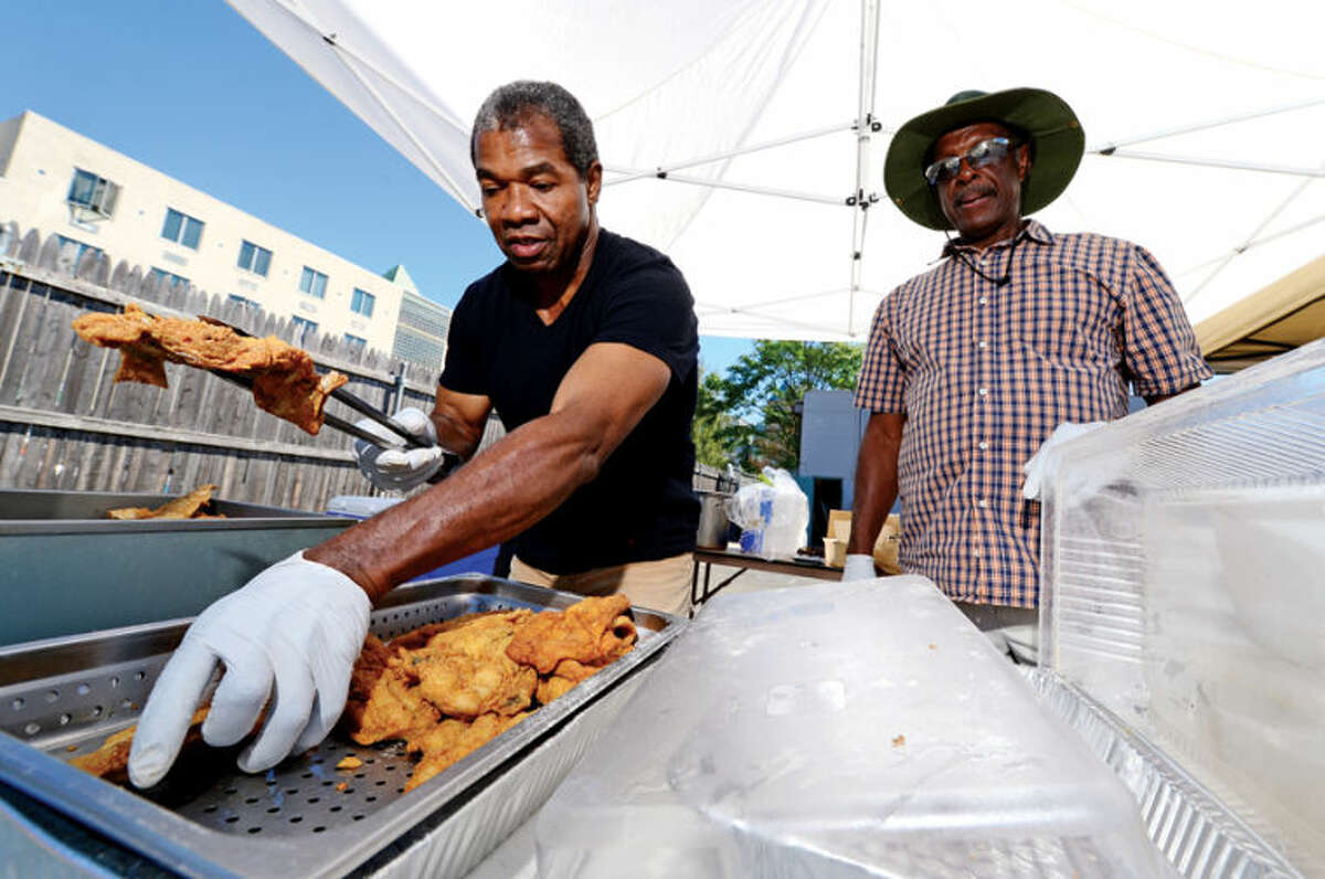 Clarence Bowden and Eddy Allen fry up fish for the Calvary Baptist Church Fish Fry fundraiser Saturday to benefit the church's youth programs. Hour photo / Erik Trautmann