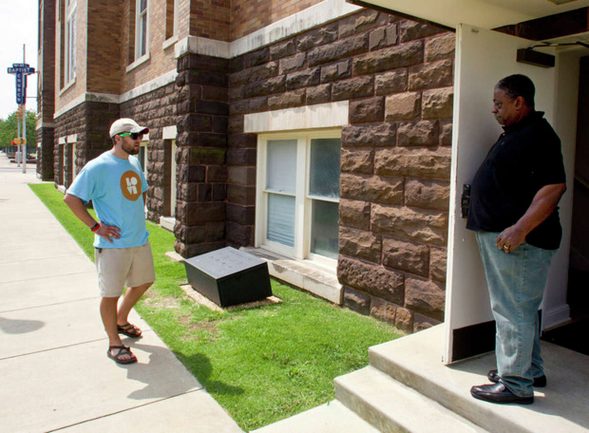 ADVANCE FOR USE SUNDAY, AUG. 25, 2013 AND THEREAFTER - Isaiah Perry, right, tells the history of the 1963 bombing of the Sixteenth Street Baptist Church in Birmingham, Ala. to tourist Josh Davis, of Lewisville, Texas, at the church on Tuesday, Aug. 6, 2013. (AP Photo/Butch Dill)