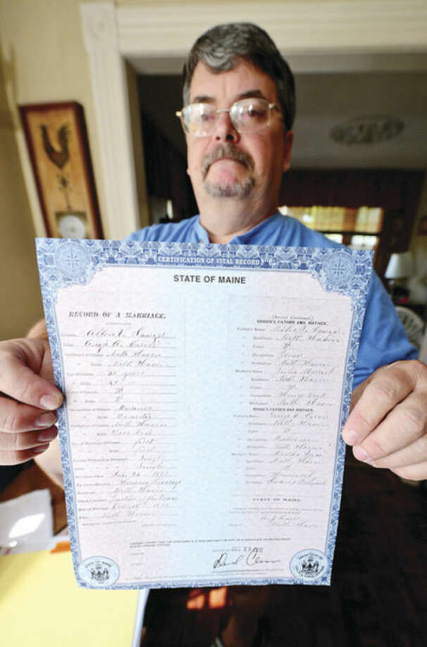 Chris Burr displays one of the oldest documents he found in his genealogy research, a marriage certificate from 1893. Burr is descended from one of Norwalk's oldest families and can trace his lineage back to Thomas Fitch. Hour photo / Erik Trautmann
