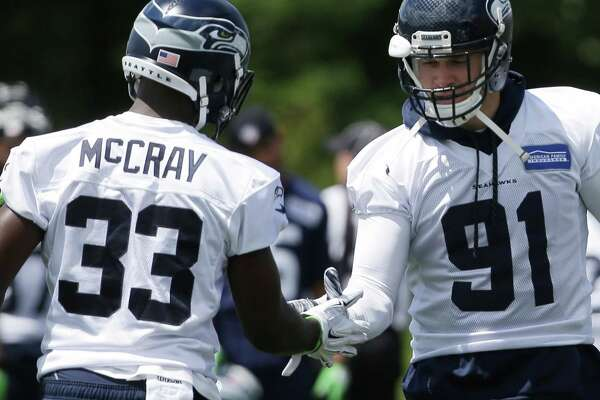 Seahawks strong safety Kelcie McCray (33) greets defensive end Cassius Marsh (91) during the team's minicamp at Virginia Mason Athletic Center in Renton, Wa., Tuesday, June 14, 2016.