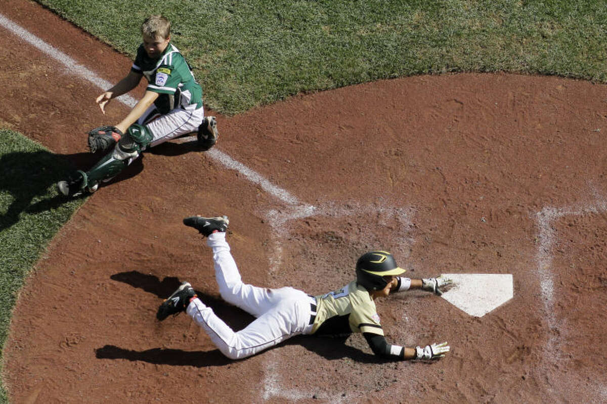 Sammamish, Wash.'s Dylan Matsuoka, bottom, scores past Westport, Conn.'s Matt Stone on a RBI-single by Jack Carper during the fourth inning of an elimination baseball game at the Little League World Series tournament, Friday, Aug. 23, 2013, in South Williamsport, Pa. Westport won 14-13 in seven innings. (AP Photo/Matt Slocum)