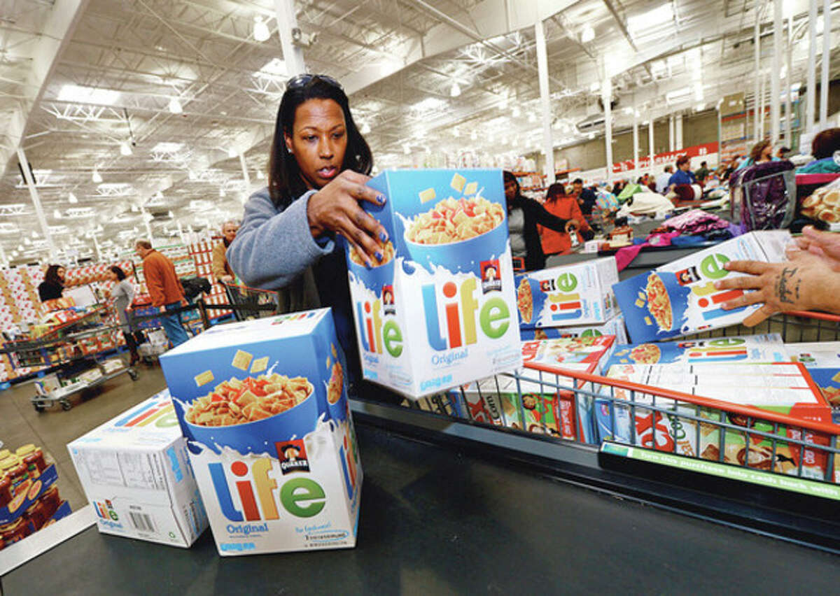 Priceline employees including Michelle Wright check out food puchases for their 8th annual Thanksgiving shopping spree to benefit the Connecticut Food Bank. Hour photo / Erik Trautmann
