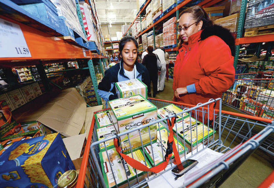 Priceline employees, including Spandana Suddapalli and Louisa Boetus, load up food for the company's 8th annual Thanksgiving shopping spree to benefit the Connecticut Food Bank.Hour photo / Erik Trautmann / (C)2012, The Hour Newspapers, all rights reserved