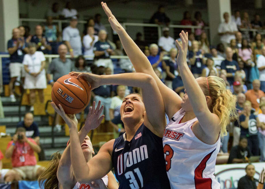 Connecticut's Stefanie Dolson, center, works under the net against pressure from Marist's guard Casey Dulin, left, and forward Emma O'Connor during the first half of an NCAA women's college basketball game in St. Thomas, U.S. Virgin Islands, Friday, Nov. 23, 2012. (AP Photo/Thomas Layer) / AP
