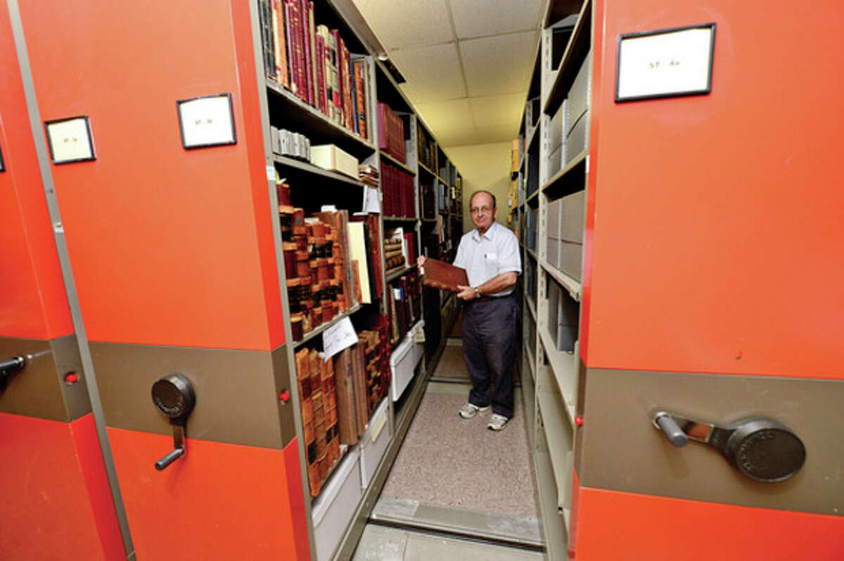 Hour photo / Erik Trautmann Town historian and library volunteer Ralph Bloom looks over records of 19th century manufacturing in Norwalk in the library's new History Room.