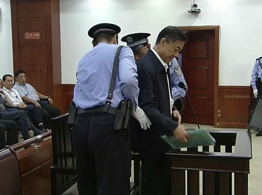 In this image taken from video, former Chinese politician Bo Xilai, center, is escorted by court guards before he sits at a defendant's seat for his trial at Jinan Intermediate People's Court in Jinan, eastern China's Shandong province, Sunday, Aug. 25, 2013. Bo on Sunday sought to discredit his former top aide as a lying, unreliable witness as the ousted leader denied criminal responsibility in the country's messiest political scandal in decades.decades. (AP Photo/CCTV via AP Video) CHINA OUT, TV OUT / CCTV via AP Video