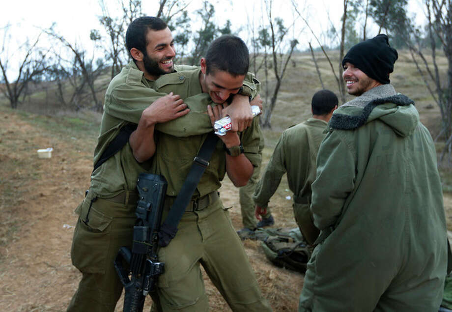 An Israeli soldier, left, hugs a comrade, center, to congratulate him for his birthday at a staging area near the Israel Gaza Strip Border, southern Israel, Thursday, Nov. 22, 2012. A cease-fire agreement between Israel and the Gaza Strip's Hamas rulers took effect Wednesday night, bringing an end to eight days of the fiercest fighting in years and possibly signaling a new era of relations between the bitter enemies. (AP Photo/Lefteris Pitarakis) / AP