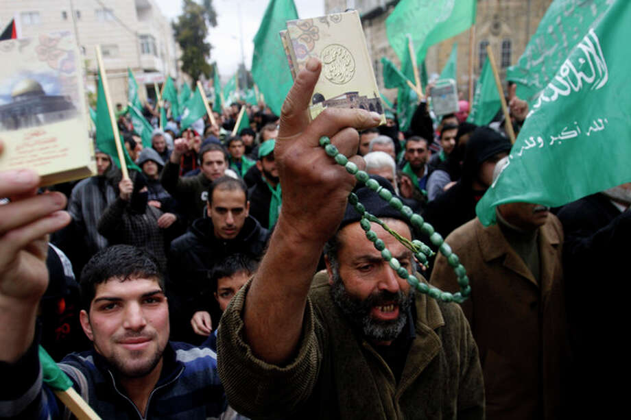 Hamas supporters wave the movement's flags and hold up Qurans during a pro-Hamas rally in the West Bank city of Hebron, Friday , Nov 23, 2012. (AP Photo/Nasser Shiyoukhi) / AP