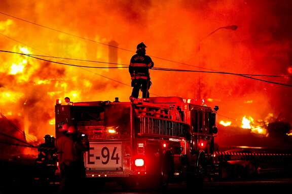 A Daly City firefighter stands atop an engine to survey the fire on Claremont Drive in San Bruno, where a suspected explosion in a gas line ignited the area.A Daly City firefighter stands atop an engine to survey the carnage of the gas pipeline explosion.