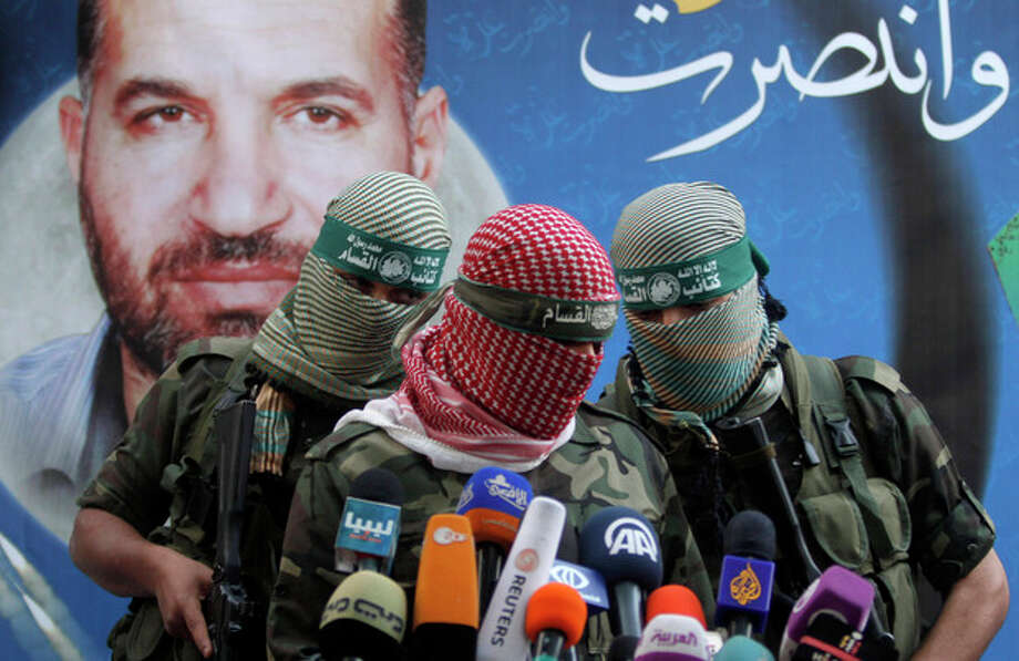 "A Hamas militant talks during a press conference in Gaza City, Thursday, Nov. 22, 2012. Gazans are celebrating a cease-fire agreement reached with Israel to end eight days of the fiercest fighting in nearly four years constricting the Gaza Strip. The poster behind him reads: ""Gaza won"" and shows the picture of Ahmed Jabari,a Hamas leader assassinated on Nov.14, setting off the last round of fighting between Israel and Hamas . (AP Photo/Hatem Moussa) / AP"