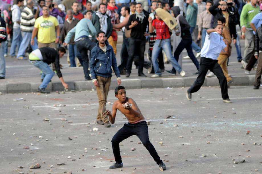 Protesters hurl stones during clashes between supporters and opponents of President Mohammed Morsi in Alexandria, Egypt, Friday, Nov. 23, 2012. Opponents and supporters of Mohammed Morsi clashed across Egypt on Friday, the day after the president granted himself sweeping new powers that critics fear can allow him to be a virtual dictator. Thousands from the two camps threw stones and chunks of marble at each other outside a mosque in the Mediterranean city of Alexandria after Friday Muslim prayers.(AP Photo/Tarek Fawzy) / AP