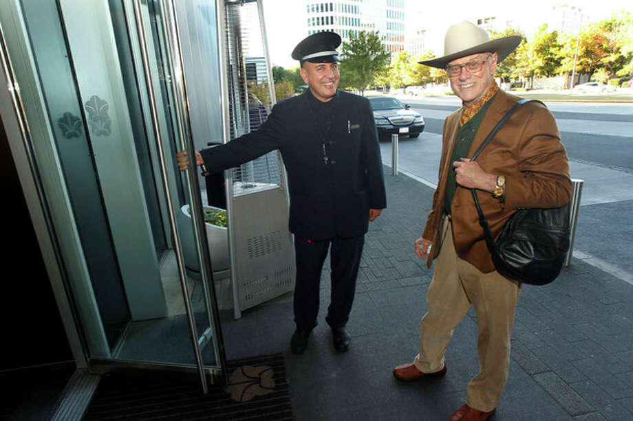 Door man Malik Fawzi greets actor Larry Hagman at the Omni Dallas Hotel in Dallas, TX on Nov. 7, 2012, as the hotel was preparing to celebrate its one year anniversary. Hagman, who for more than a decade played villainous patriarch JR Ewing in the TV soap Dallas, has died at the age of 81, his family said Saturday Nov. 24, 2012. (AP Photo/Michael Ainsworth/The Dallas Morning News) / Dallas Morning News