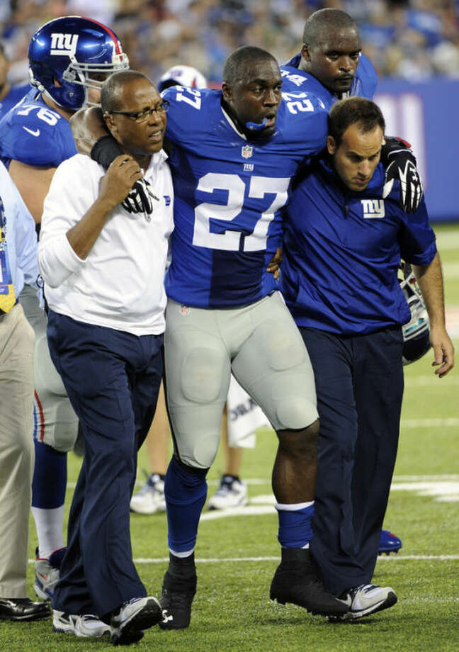 Trainers carry New York Giants safety Stevie Brown (27) off the field after he was injured on a play during the first half of a preseason NFL football game against the New York Jets, Saturday, Aug. 24, 2013, in East Rutherford, N.J. (AP Photo/Bill Kostroun)