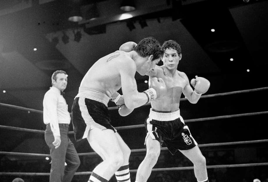"FILE - In this July 11, 1982 file photo, Luis Loy Jr., left, ducks under a blow by Hector Camacho early in a scheduled 10-round junior lightweight boxing bout at Felt Forum in New York. Hector ""Macho"" Camacho, a boxer known for skill and flamboyance in the ring, as well as for a messy personal life and run-ins with the police, has died, Saturday, Nov. 24, 2012, after being taken off life support. He was 50. (AP Photo/Elias, File) / AP"
