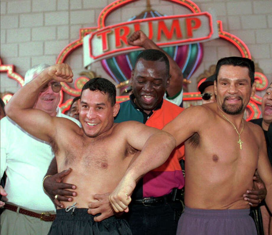 """FILE - In this June 21, 1996 file photo, after a ceremonial weigh-in, Panamanian Roberto Duran, right, reaches for the stomach of boxing champ Hector """"Macho"""" Camacho, left, who tries to elbow Duran's hand away at the Trump Taj Mahal Casino Resort in Atlantic City, N.J. Camacho, a boxer known for skill and flamboyance in the ring, as well as for a messy personal life and run-ins with the police, has died, Saturday, Nov. 24, 2012, after being taken off life support. He was 50. (AP Photo/Charles Rex Arbogast, File) / AP"""