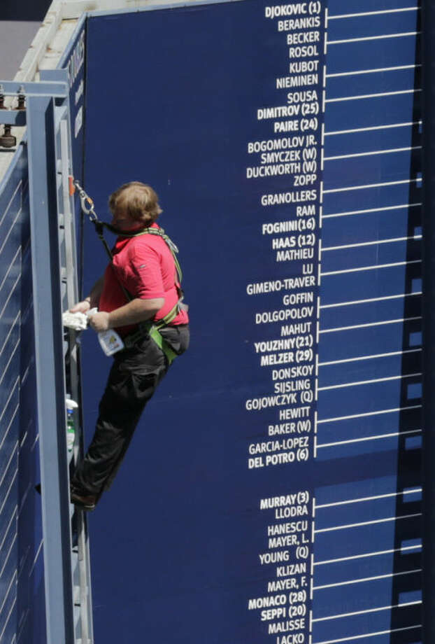 A worker prepares a scoreboard the day before the start of the 2013 US Open tennis tournament Sunday, Aug. 25, 2013, in New York. (AP Photo/Charles Krupa)