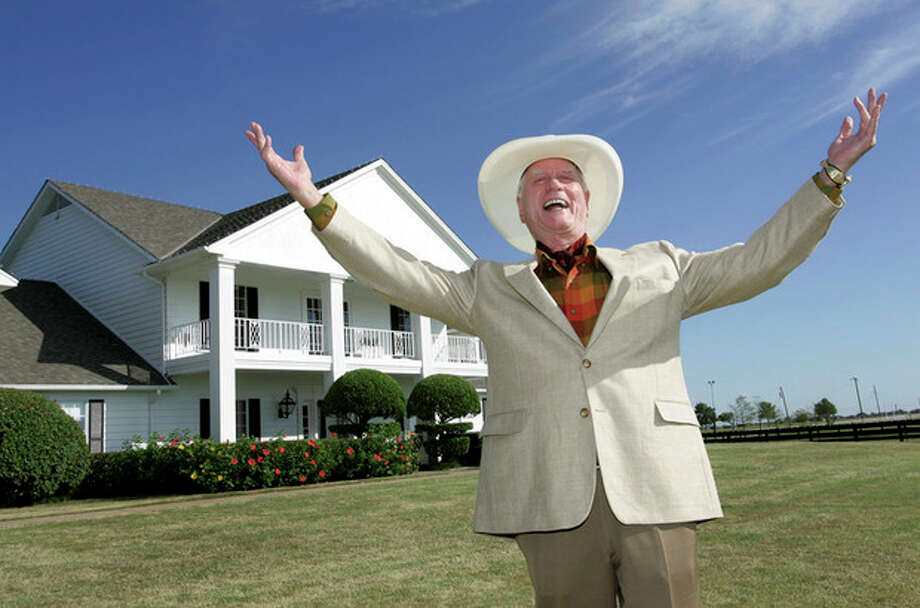 "FILE - In this Oct. 9, 2008 file photo, actor Larry Hagman poses in front of the Southfork Ranch mansion in Parker, Texas made famous in the television show ""Dallas."" Actor Larry Hagman, who for more than a decade played villainous patriarch JR Ewing in the TV soap Dallas, has died at the age of 81, his family said Saturday Nov. 24, 2012. (AP Photo/Tony Gutierrez, File) / AP"
