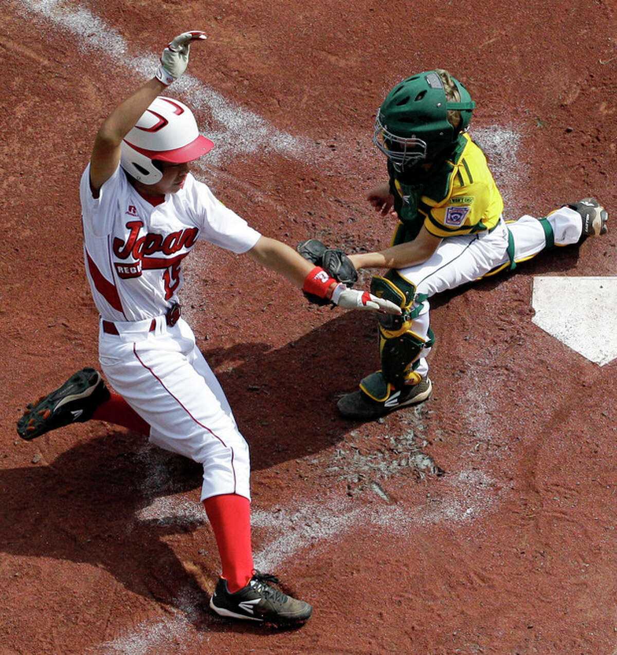 Tokyo, Japan's Takuma Gomi (15) is tagged out by Chula Vista, Calif., catcher Patrick Archer, right, while attempting to score on a wild pitch in the first inning of the Little League World Series Championship baseball game in South Williamsport, Pa., Sunday, Aug. 25, 2013. (AP Photo/Gene J. Puskar)