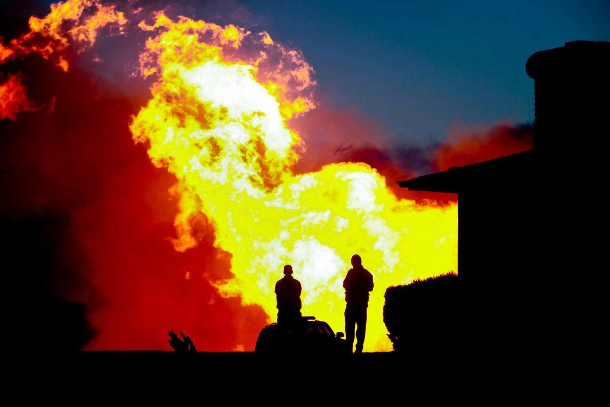 Smoke and fire can be seen after an explosion near Skyline Blvd and San Bruno Avenue in San Bruno, Calif., on Thursday, September 9, 2010.People standing on Claremont Street watch smoke and fire shoot into the sky. One observer estimated that flames were shooting 200 to 300 feet into the air.