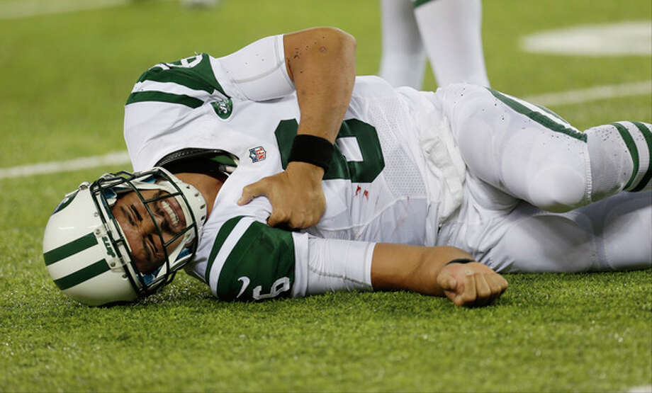 New York Jets quarterback Mark Sanchez (6) reacts to an injury during the second half of a preseason NFL football game against the New York Giants, Saturday, Aug. 24, 2013, in East Rutherford, N.J. He left the game with what appeared to be a shoulder injury. (AP Photo/Julio Cortez) / AP