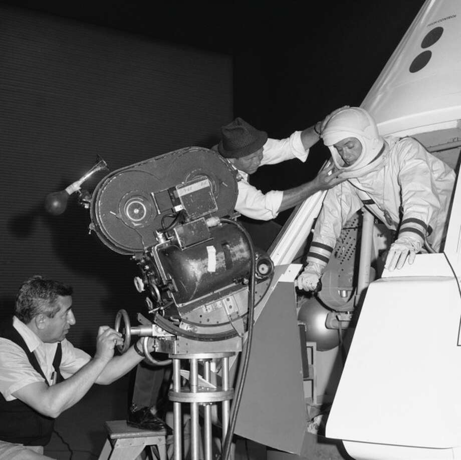 "FILE - In this June 4, 1965 file photo, from left, cameraman Sam Rosen and director Gero Nelson guide the co-star of the series ""I Dream of Jeannie,"" Larry Hagman, as he emerges from a mockup of the Apollo space vehicle, filming at North American Aviation's Space Division in Downey, Calif. (AP Photo/File) / AP"