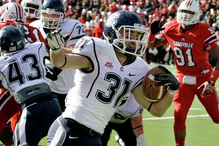Connecticut wide receiver Nick Williams (31) celebrates as he skips into the end zone untouched to score on a 3-yard run against Louisville during the first half of an NCAA college football game in Louisville, Ky., Saturday, Nov. 24, 2012. (AP Photo/Garry Jones) / FR50389 AP
