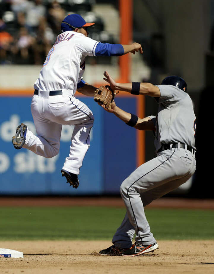 New York Mets shortstop Omar Quintanilla, left, turns a double play over Detroit Tigers' Omar Infante, right, during the sixth inning of an interleague baseball game at Citi Field, Sunday, Aug. 25, 2013, in New York. (AP Photo/Seth Wenig)