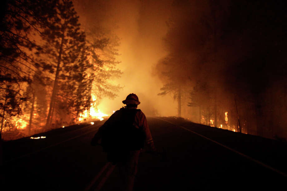 A firefighter walks along Highway 120 past burning trees as firefighters continues to battle the Rim Fire near Yosemite National Park, Calif., on Sunday, Aug. 25, 2013. Fire crews are clearing brush and setting sprinklers to protect two groves of giant sequoias as a massive week-old wildfire rages along the remote northwest edge of Yosemite National Park. (AP Photo/Jae C. Hong) / AP