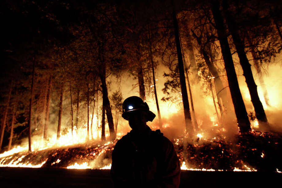 A firefighter watches for spot fires during a burnout operation while battling the Rim Fire near Yosemite National Park, Calif., on Sunday, Aug. 25, 2013. Fire crews are clearing brush and setting sprinklers to protect two groves of giant sequoias as a massive week-old wildfire rages along the remote northwest edge of Yosemite National Park. (AP Photo/Jae C. Hong) / AP