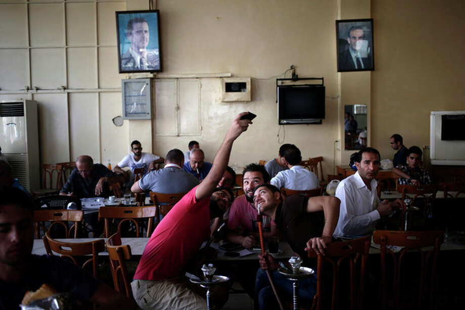 Friends pose for a photograph at coffee shop in Damascus, Syria, Sunday, Aug. 25, 2013. Syria reached an agreement with the United Nations on Sunday to allow a U.N. team of experts to visit the site of alleged chemical weapons attacks last week outside Damascus, state media said. (AP Photo/Hassan Ammar) / AP