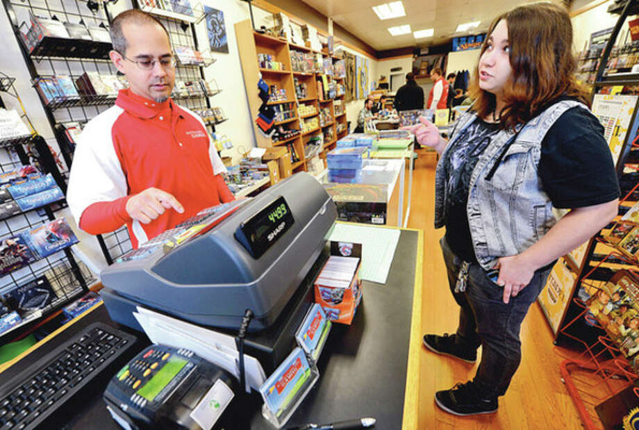 Hour photo / Erik TrautmannSteven Bryant, owner of Battleground Gaming, rings up customer Amanda Swift with a discount for Small Business Saturday. This is the shopping day between Black Friday and Cyber Monday that is dedicated to supporting small businesses nationwide with help from American Express. Last year, more than 100million people came together to Shop Small in their communities on Small Business Saturday. / (C)2012, The Hour Newspapers, all rights reserved
