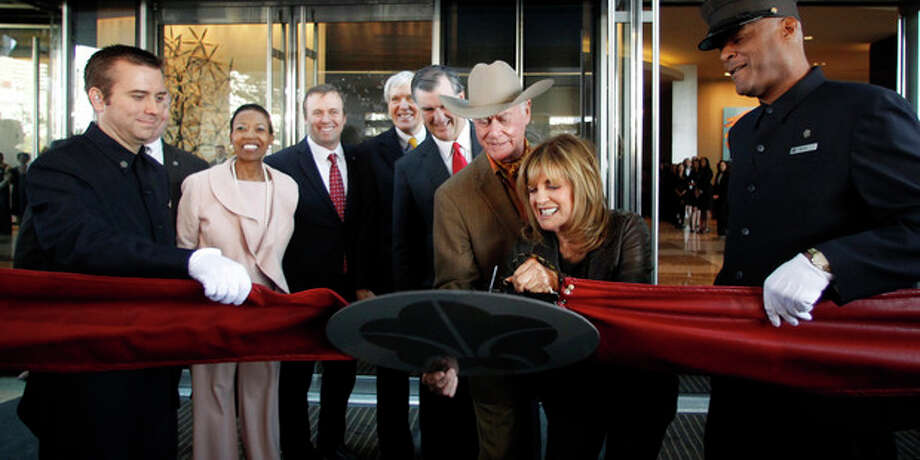 Linda Gray cuts the ribbon as Larry Hagman holds the ribbon at the grand opening of the Omni Dallas Hotel on Friday, November 11, 2011. In the background, Hattie Hill, Chairman of the Dallas Convention & Visitors Bureau, Jack Matthews, Former Dallas Mayor Tom Leppert, and Dallas Mayor Mike Rawlings look on. Hagman, who for more than a decade played villainous patriarch JR Ewing in the TV soap Dallas, has died at the age of 81, his family said Saturday Nov. 24, 2012. (AP Photo/David Woo, The Dallas Morning News) / The Dallas Morning News