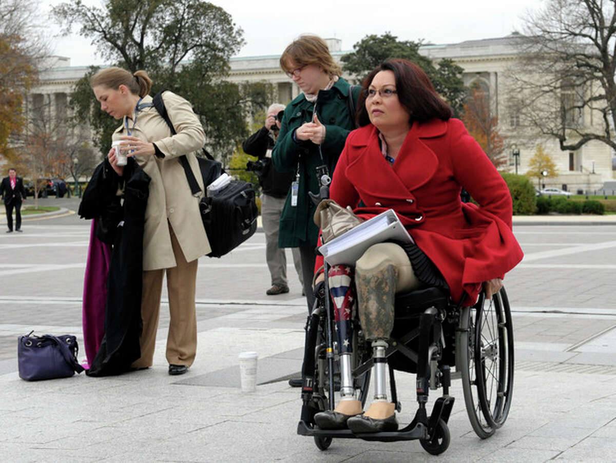 FILE - This Nov. 15, 2012 file photo shows Iraq war veteran, Rep.-elect Tammy Duckworth, D-Ill., who lost both legs in combat before turning to politics, arriving for a group photo on the East steps of the Capitol in Washington. Veterans groups say the influx of Iraq and Afghanistan veterans in Congress is welcome because it comes at a time when the overall number of veterans in Congress is on a steep and steady decline. In the mid-1970s, the vast majority of lawmakers tended to be veterans. (AP Photo/Susan Walsh)
