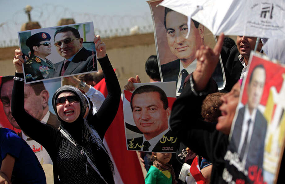 Supporters of former Egyptian President Hosni Mubarak, hold posters of him as they protest outside the Cairo Police Academy--turned--court, Cairo, Egypt, Sunday, Aug. 25, 2013. Mubarak, under house arrest after being released from detention last week, is standing retrial in charges of complicity in the killings of protesters during 2011 Egyptian uprising.(AP Photo/Khalil Hamra) / AP