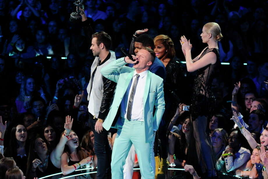 """Ryan Lewis, left, Macklemore, center, and Ray Dalton accept the award for best hip hop video for """"Can't Hold Us"""" as presenters Iggy Azalea, right, and Lil' Kim look on, at the MTV Video Music Awards on Sunday, Aug. 25, 2013, at the Barclays Center in the Brooklyn borough of New York. (Photo by Charles Sykes/Invision/AP) / Invision"""