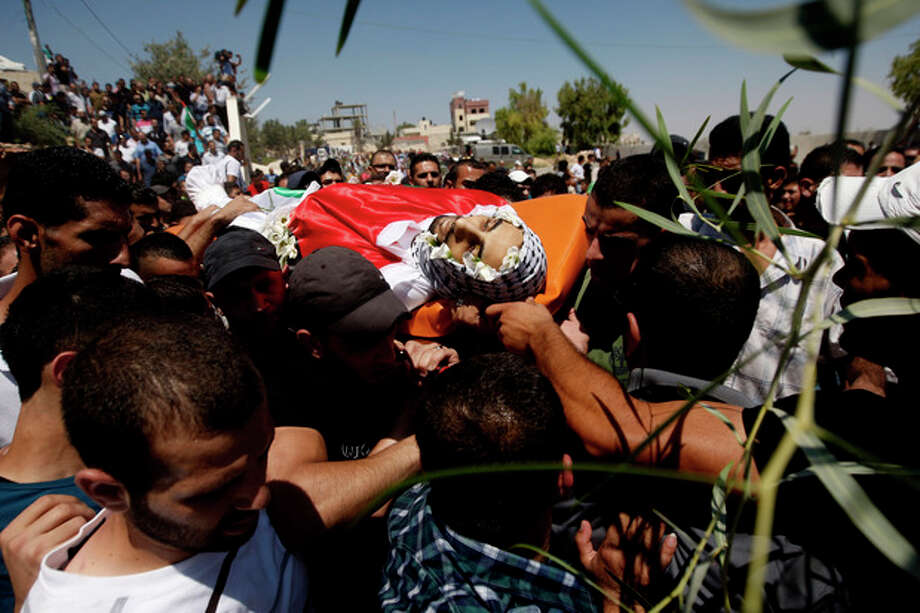 Palestinian mourners carry the body of one of three slain Palestinians, during their funeral procession in the Qalandia refugee camp, at the outskirts of the West Bank town of Ramallah, Monday, Aug. 26, 2013. Israeli soldiers killed three Palestinians in clashes during an arrest raid in the West Bank, a Palestinian official and the Israeli military said Monday, in the deadliest incident in the area in years. (AP Photo/Majdi Mohammed) / AP