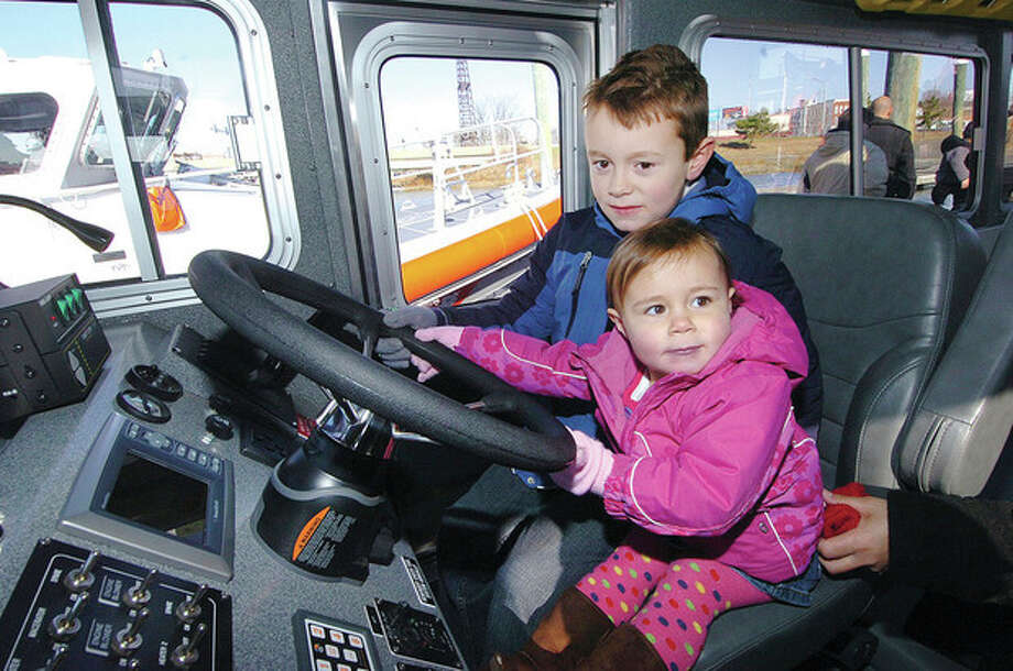 Hour Photo Alex von Kleydorff; 7yr old Robert and 2yr old Kyla Bedell see how it feels behind the wheel of the new fire boat as its commissioned in their Grandfathers name, Robert Bedell, at Veterans Memorial Park in Norwalk Monday / 2012 The Hour Newspapers