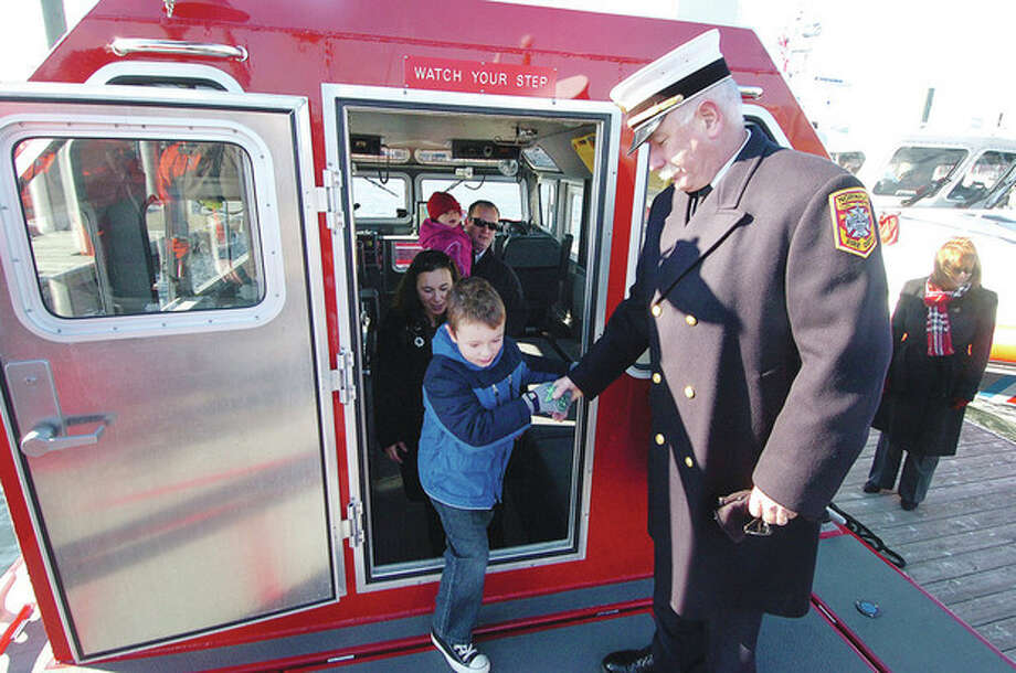 Hour Photo Alex von Kleydorff; After a commissioning at Veterans Park , Norwalk Fire Chief Denis McCarthy helps 7yr old Robert Bedell from the cabin of the department's new MU238 fire boat named for Bedell's Grandfather Robert. / 2012 The Hour Newspapers